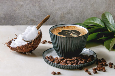 Bulletproof coffee. Keto diet coffee in blue ceramic cup with organic coconut cold press oil in spoons with beans and green branch on white marble table. Grey wall at background.