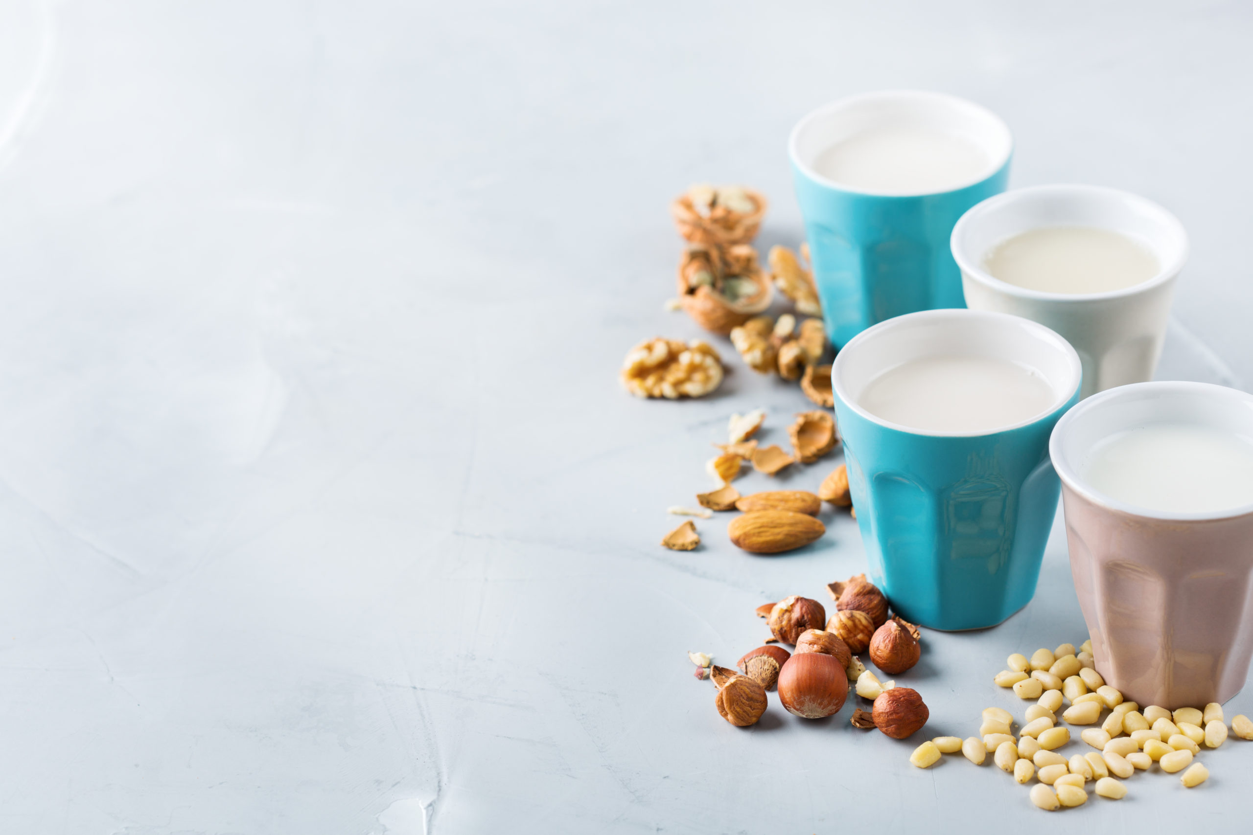 Food and drink, health care, diet and nutrition concept. Assortment of organic vegan non diary milk from nuts in glasses on a kitchen table. Copy space background