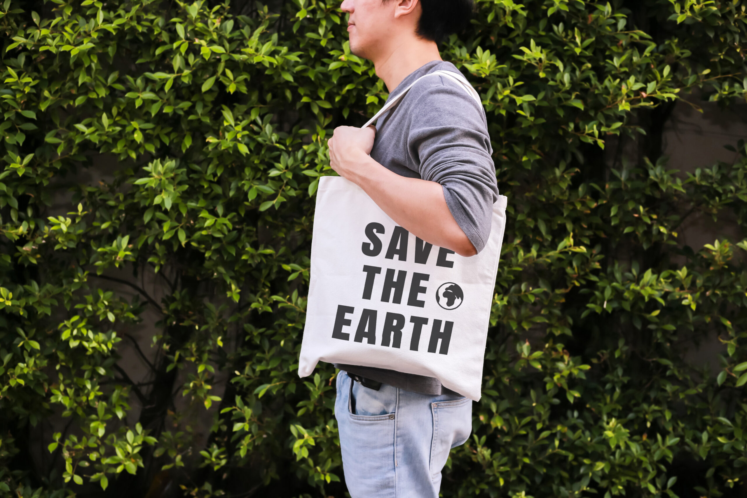 Young male hipster holding and carrying the Save The Earth tote handbag in green nature environment background – ecology and recycle concept